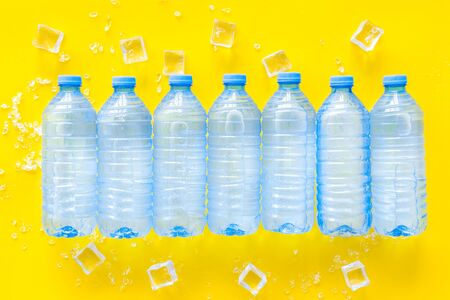 Pure frozen water in plastic bottles on yellow background top view