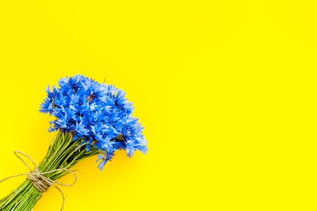Summer. Field flowers design with bouquet of blue cornflowers on yellow background top view space for text