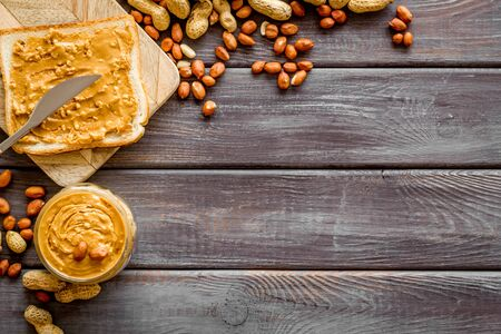 peanut butter for cooking breakfast with sandwiches at home on wooden background top view mock-up.