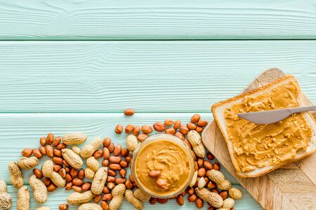 peanut butter for cooking breakfast with sandwiches at home on mint green wooden background top view mock-up 写真素材