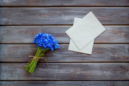 Field flowers design with bouquet of blue cornflowers and envelopes for present on wooden background top view mock-up Reklamní fotografie