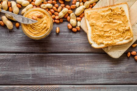 peanut butter for cooking breakfast with sandwiches at home on wooden background top view mock-up 写真素材