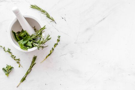 Alternative medicine with medicinal herbs on white marble background top view mock up
