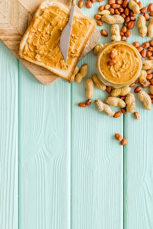 sandwiches with peanut butter for breakfast on mint green wooden background top view space for text