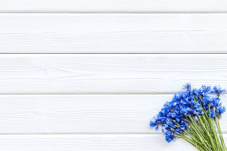 Blue cornflowers for floral design on white wooden background top view mockup