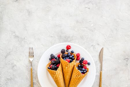 Fresh berries in waffle cones on plate with fork and knife on light stone kitchen table background top view mock up