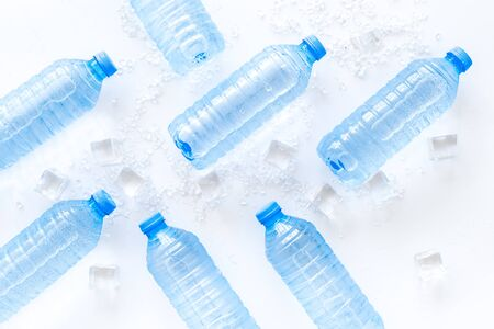 empty plastic bottles for pure water with ice cubes on white background top view pattern