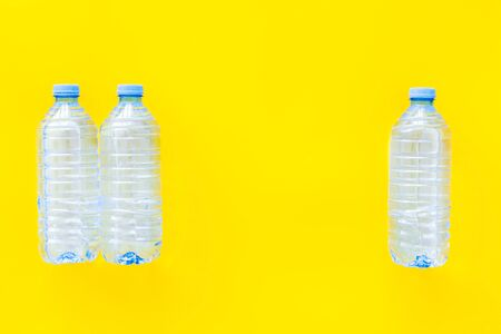 empty plastic bottles for pure water on yellow background top view mock up
