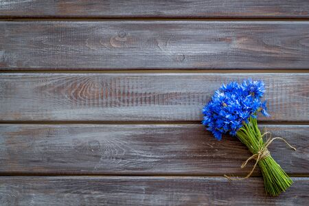 Summer design for blog with bouquet of blue cornflowers on wooden background top view copyspace