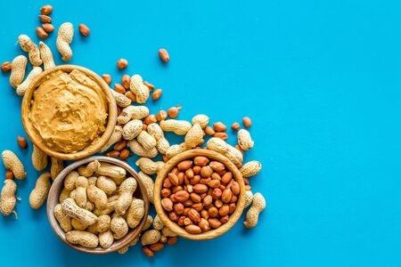 nuts in bowl for peanut butter for cooking breakfast at home on blue background top view mock-up