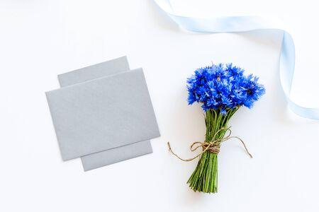 Bouquet of blue cornflowers, envelopes on white background top view mockup Reklamní fotografie