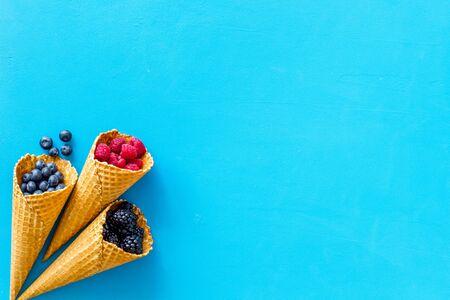 Summer breakfast with fresh berries in waffle cones on blue background top view mockup 版權商用圖片