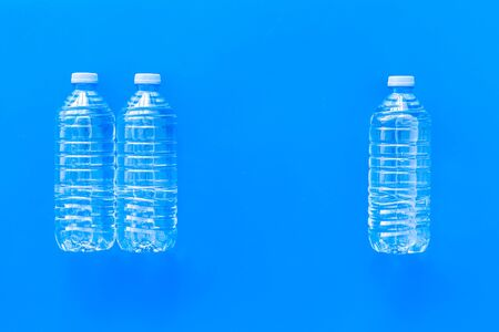 Pure water in plastic bottles on blue background top view copyspace