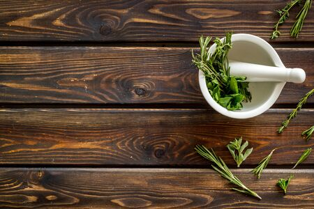 Homeopathy with leaves and healing herbs for making oil on wooden background top view copyspace