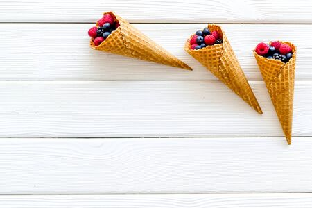 Summer breakfast with fresh berries in waffle cones on white wooden background top view mockup
