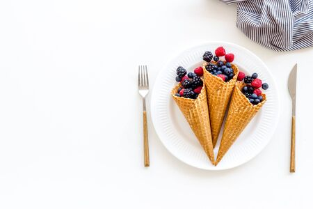 Fresh berries in waffle cones on plate with fork and knife on white kitchen table background top view mock up