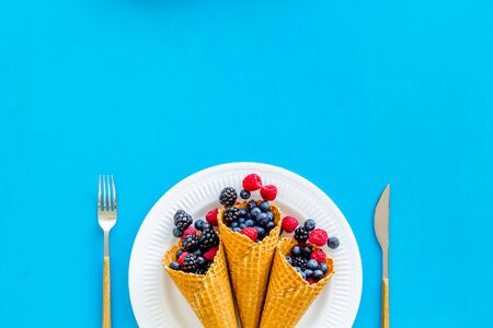 Fresh berries in waffle cones on plate with fork and knife on blue kitchen table background top view mock up