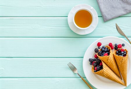 Fresh berries in waffle cones with tea and tableware on mint green wooden kitchen table background top view mock up