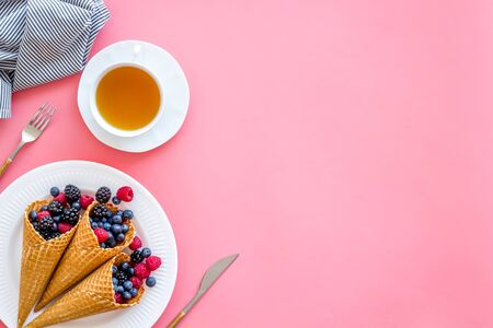 Fresh berries in waffle cones with tea and tableware on pink kitchen table background top view mock up Banco de Imagens