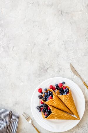 Light breakfast with fresh berries in waffle cones and tableware on served light stone table background top view mockup