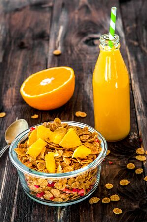 flakes in bowl with orange slices on dark wooden background