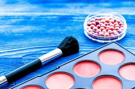 cosmetic palette and brush on wooden background