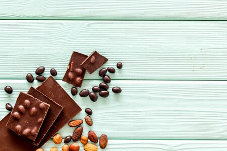 Chocolate bars and nuts on mint green wooden table background top view mockup