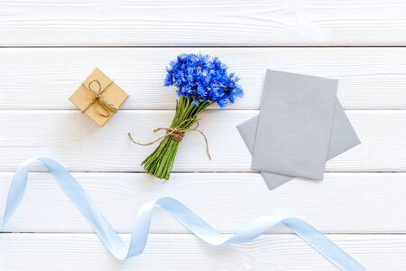 Summer flowers pattern with bouquet of blue cornflowers, envelopes and gift on white wooden background top view mock up
