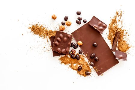 Chocolate bars and nuts on white table background top view Imagens