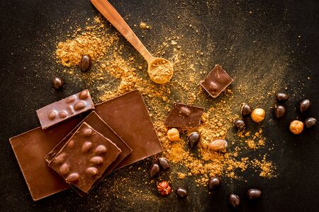 Chocolate splash bars and nuts on black table background top view Imagens