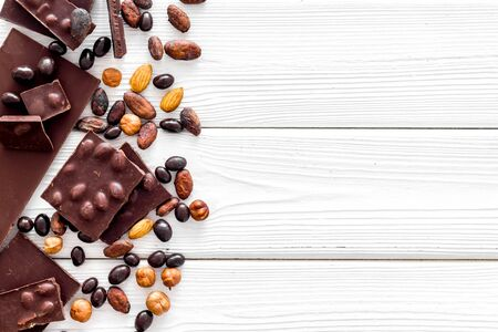 Chocolate bars and nuts on white wooden table background top view mockup