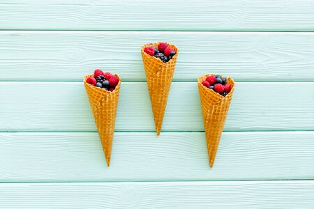Fresh berries in waffle cones on mint green wooden background top view