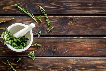 Alternative medicine. Homeopathy with leaves and healing herbs for making oil on wooden background top view copyspace