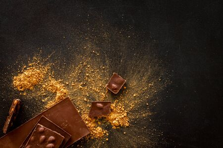 Chocolade with cocoa powder and bars on black background top view mock-up.