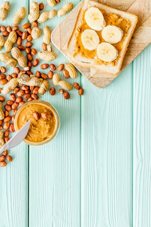 Vegan breakfast. Make sandwiches with banana and peanut butter in glass bowl, knife on mint green wooden background top view copyspace