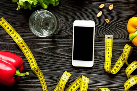 Concept diet and smartphone with vegetables mock up on wooden 写真素材