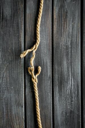 Tearing the rope under stress on wooden background top view copyspace
