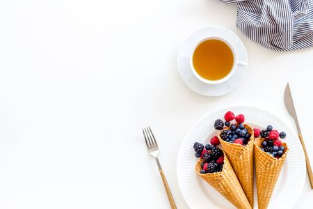 Light breakfast with fresh berries in waffle cones and cup of tea on served white table background top view mockup