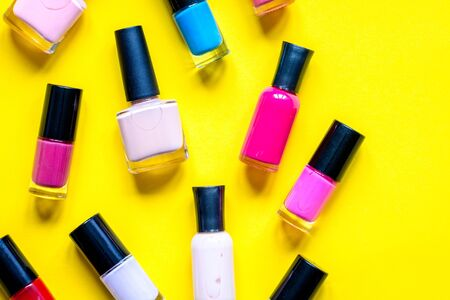 lot of bottles nail polish on yellow background top view Stockfoto
