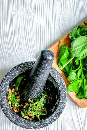 fresh herbs, avocado and mortar on wooden background top view. 免版税图像