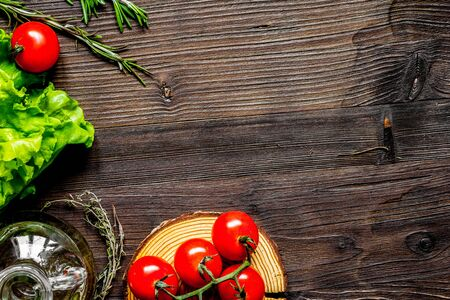 tomato, rosemary and garlic on dark wooden background top view