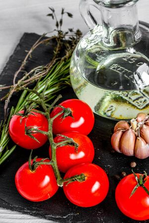 tomato with olive oil, garlic, rosemary, thyme on wooden background