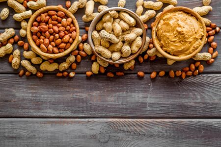 Product for hearty breakfast with peanut butter in bowl near nuts on wooden background top view mockup