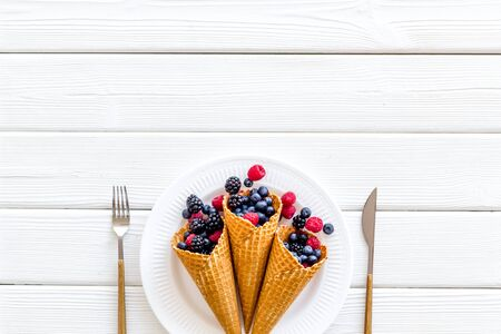 Light breakfast with fresh berries in waffle cones and tableware on served white wooden table background top view mockup Zdjęcie Seryjne