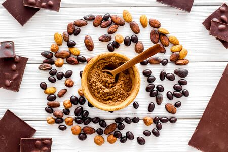 Chocolate with nuts and its ingredients on white wooden background top view