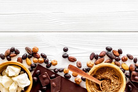 Different variety of chocolate and hazelnut on white wooden background top view space for text Zdjęcie Seryjne
