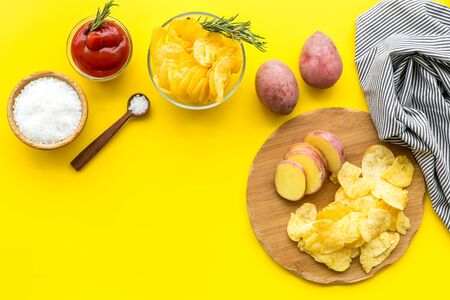 Cooking homemade potato chips with ketchup on yellow background top view copyspace
