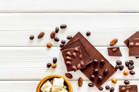 Cook homemade chocolate with bars, nuts, coffee beans on white wooden background top view mock up