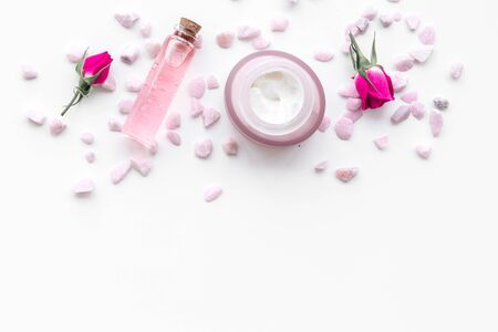 Cosmetics with sea salt and roses decoration on white background top view space for text Archivio Fotografico - 129423805