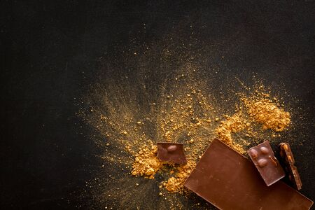Cooking chocolade with cocoa powder and bars on black background top view mock-up